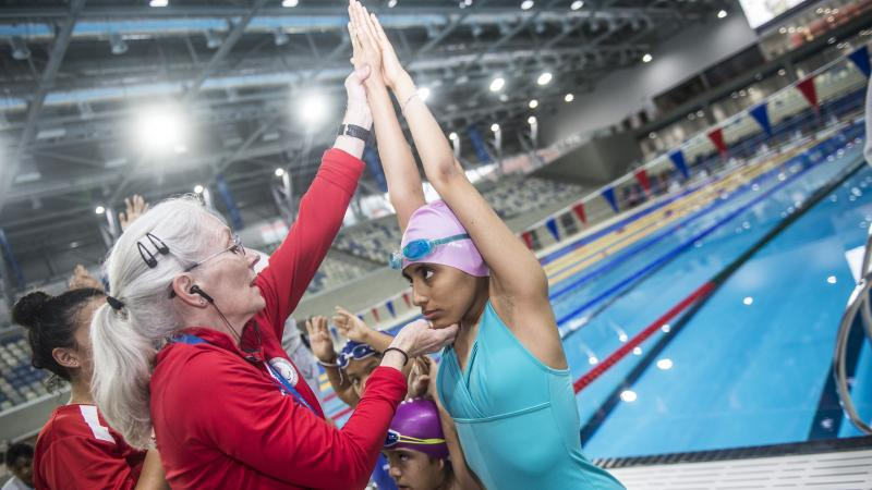 Para swimming coach interacts with athlete during Road to Lima 2019 workshop