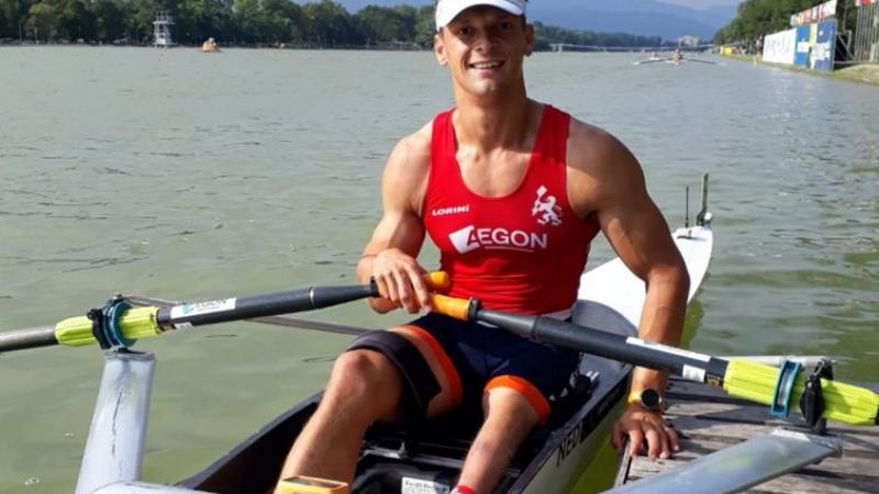 Dutch man sits in rowing boat and smiles