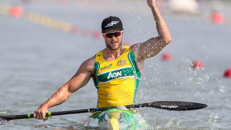 Man in kayak splashes water to celebrate victory