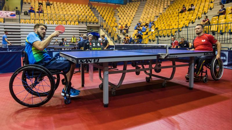 Two men in wheelchairs play table tennis