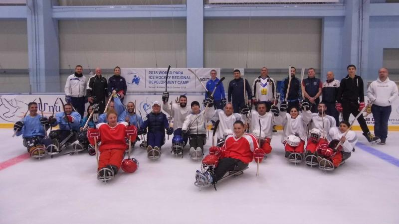 a group of Para ice hockey players sitting on the ice and raising their sticks