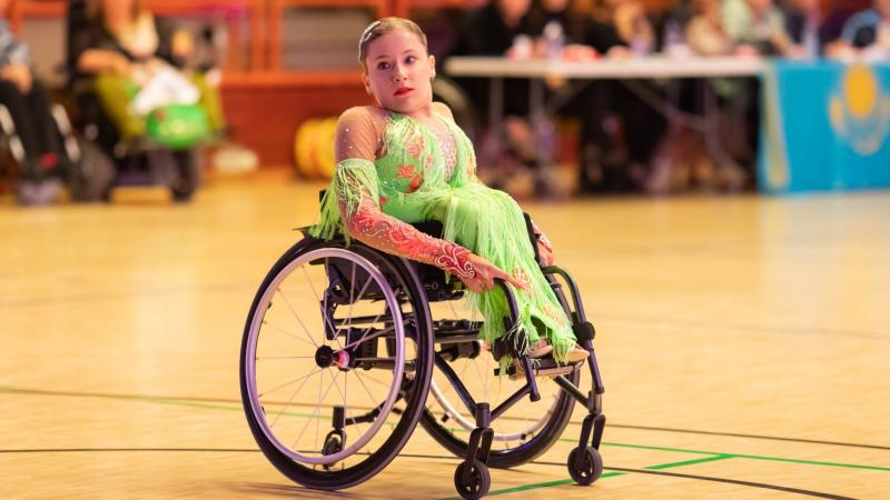 Young female Polish dancer in wheelchair looks on