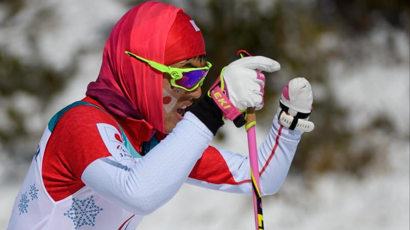 a male Para Nordic skier with one hand pushes through the snow