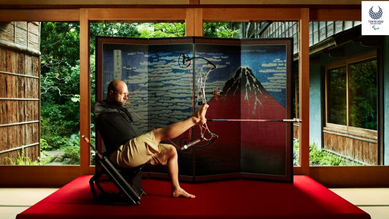 Armless archer sits down holding bow and arrow with foot with Japanese backdrop