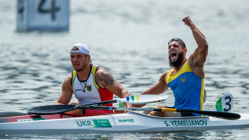 two male Para canoeists side by side in their boats with one punching the air in celebration