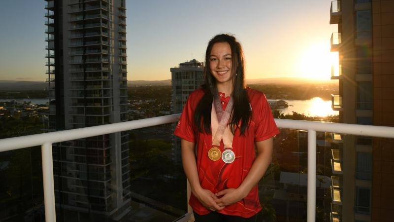 a female Para swimmer standing on a balcony with two medals around her neck