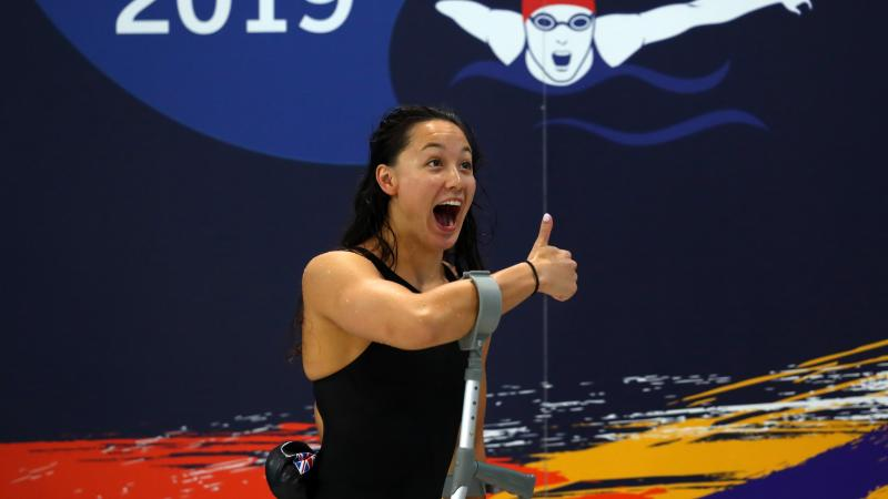 a female Para swimmer gives the thumbs up