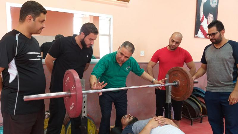 a group of officials standing round an athlete lying on a powerlifting bench