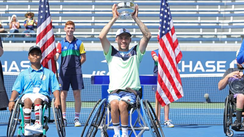 a male wheelchair tennis player holds up a trophy