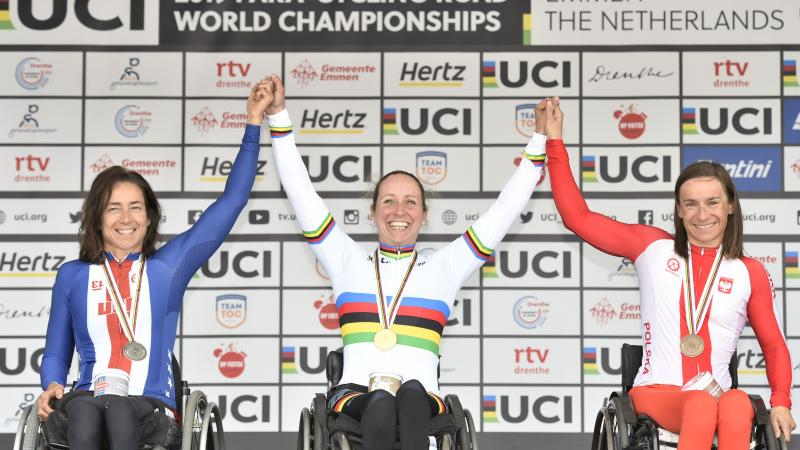 Three wheelchair cyclists hold hands on podium