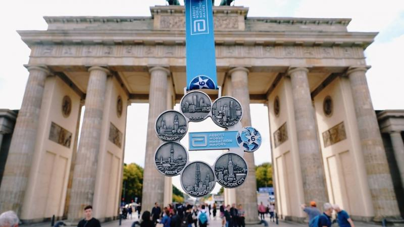 A marathon medal being shown in front of the Brandenburg Gate in Berlin
