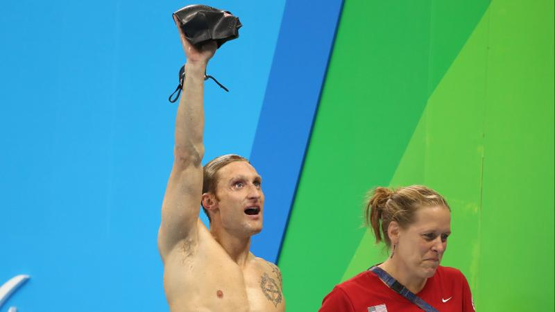 a male Para swimmer holds up his swimming cap in victory