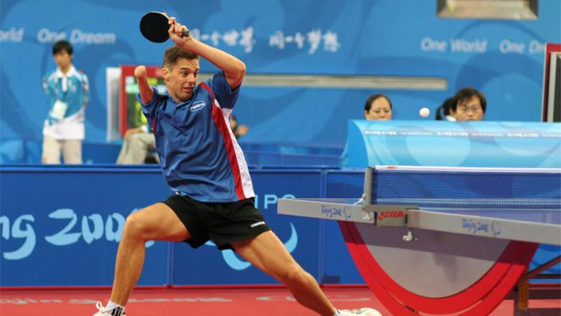 Man with right arm impairment hits a return shot in table tennis