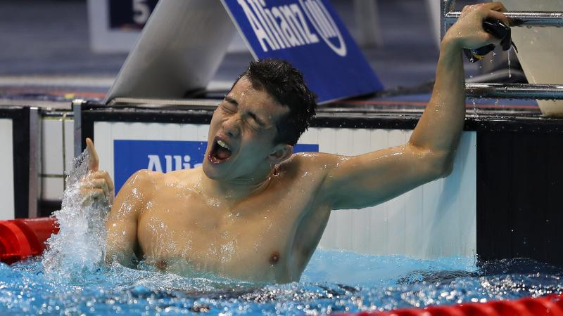 a male Para swimmer celebrates in the water