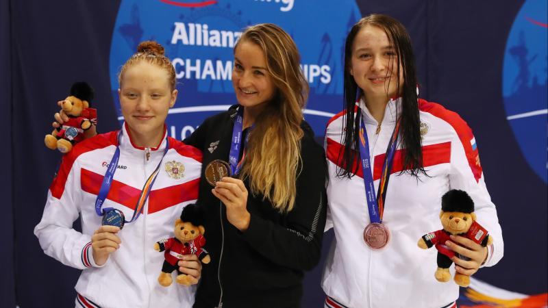 three female Para swimmers on the podium holding up their medals