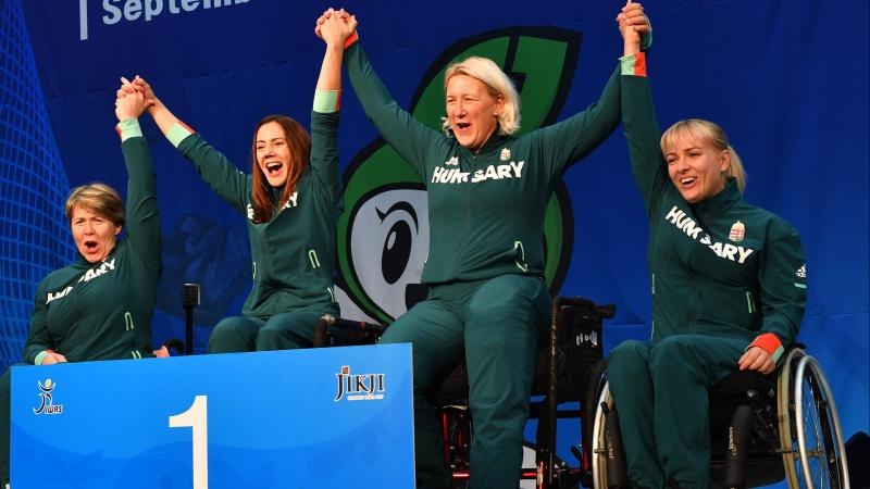 Four Hungarian female wheelchair fencers hold hands on the podium