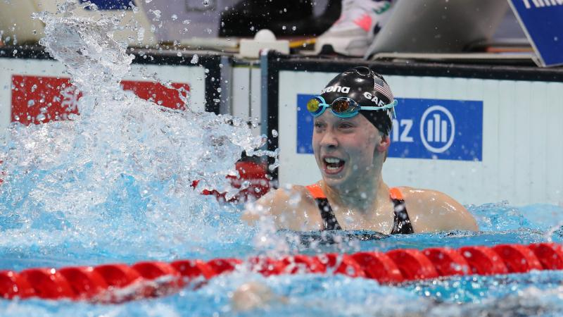 US female swimmer splashes water to celebrate