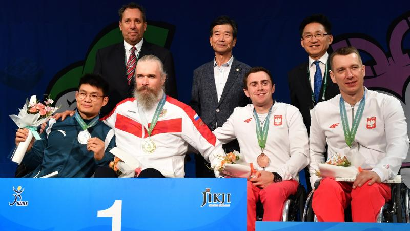 Four men in wheelchairs in a podium with three standing men behind them