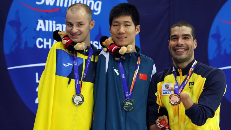 three male Para swimmers on the podium