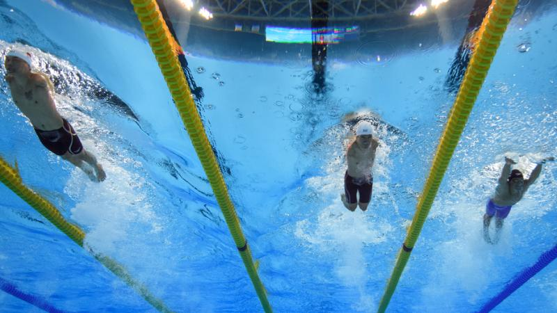 three male Para swimmers with no arms swimming breaststroke