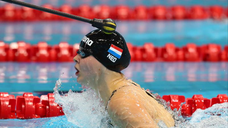a female vision impaired swimmer is tapped on the head during breaststroke