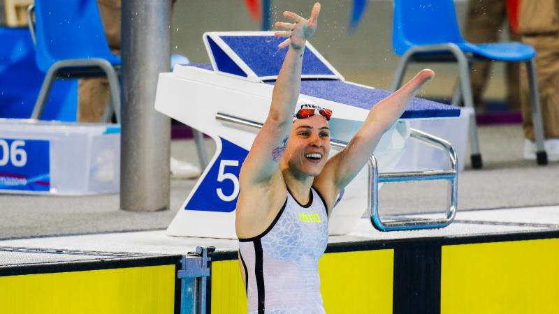 a female Para swimmer raises her arms in celebration in the pool