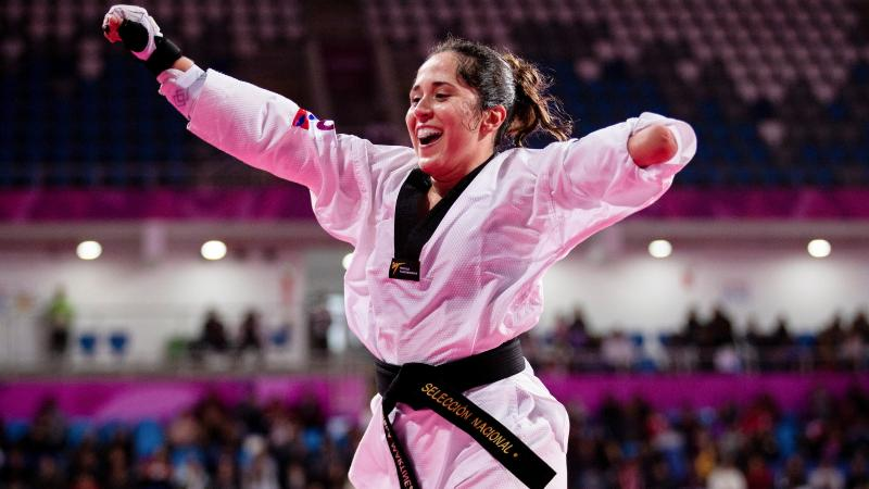 a female Para taekwondo athlete raises her arms in celebration