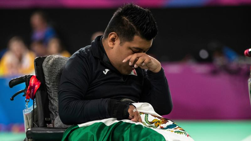 a male boccia player wipes away a tear with the Mexican flag on his lap