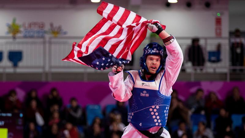 a male Para taekwondo fighter holding up the USA flag