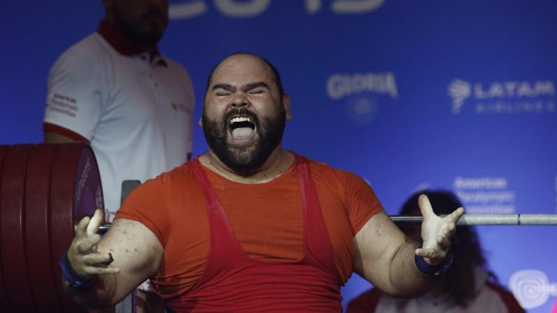 a male powerlifter celebrates on the bench