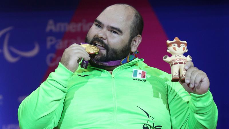 a male powerlifter bites his gold medal