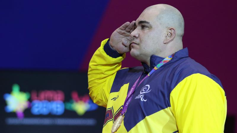 a male powerlifter salutes on the podium