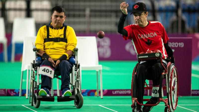 two male boccia players throwing a ball