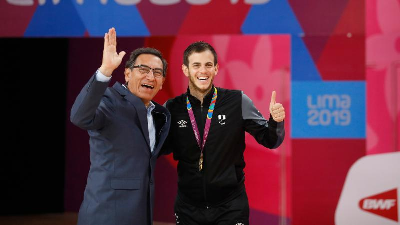 two men giving a thumbs up on the podium