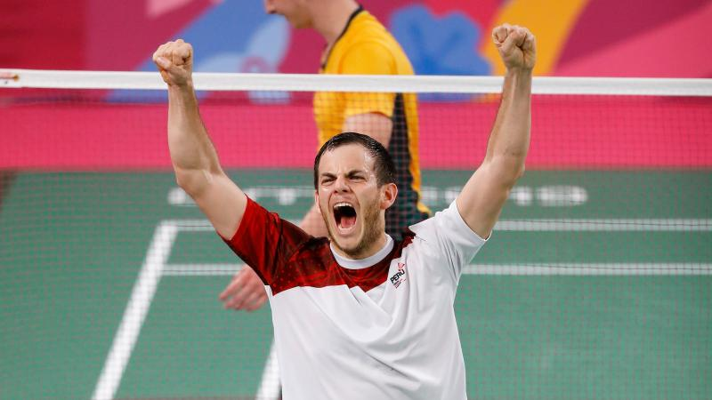 a male Para badminton player raises his arms into the air in celebration