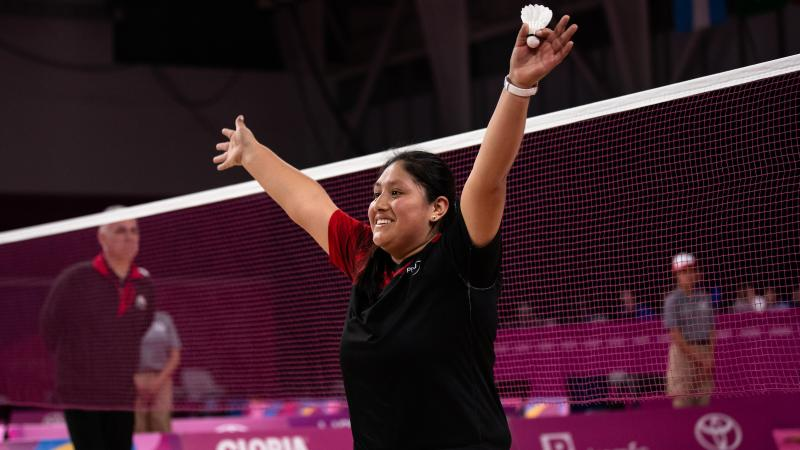 a female wheelchair badminton player throws her arms up in victory