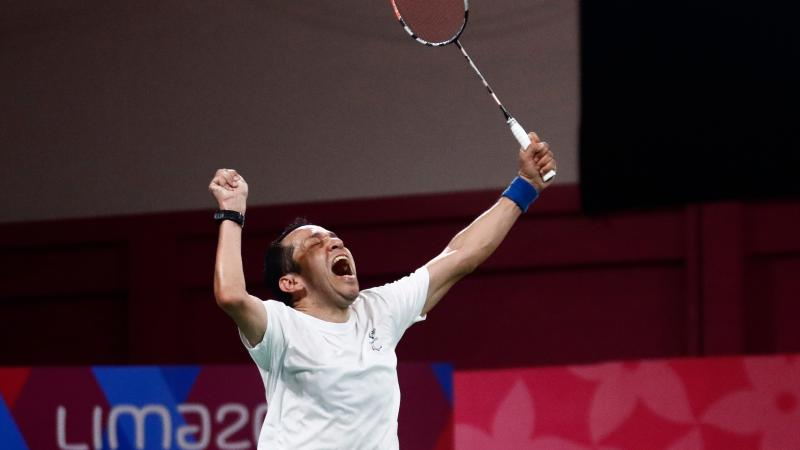 a male Para badminton player raises his fist and racquet into the air in celebration
