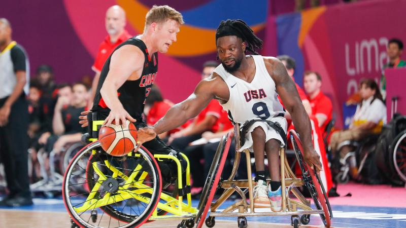 two male wheelchair basketball players fight for the ball