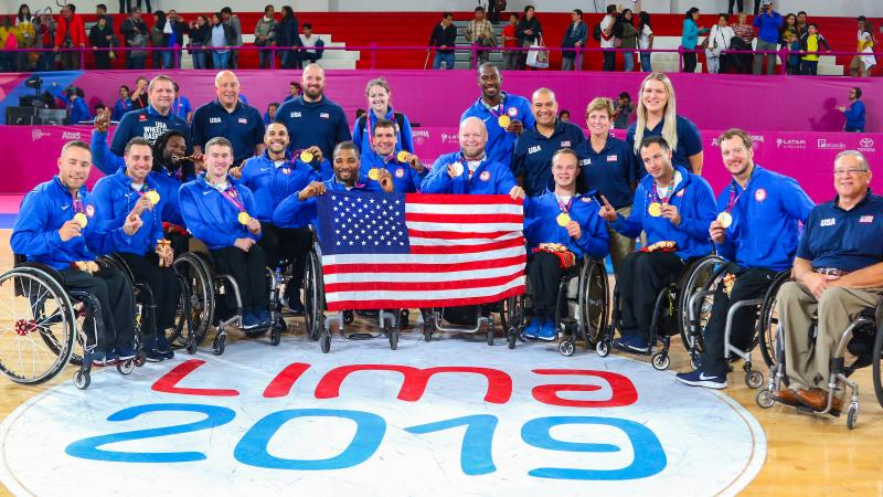 a group of male wheelchair basketball players holding their gold medals and the USA flag