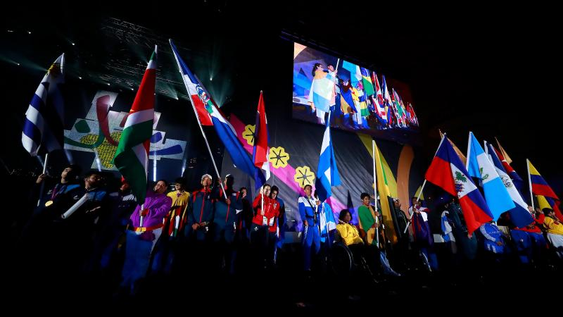 a group of athletes holding national flags