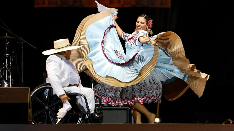 a female dancer swirls a giant skirt on a stage