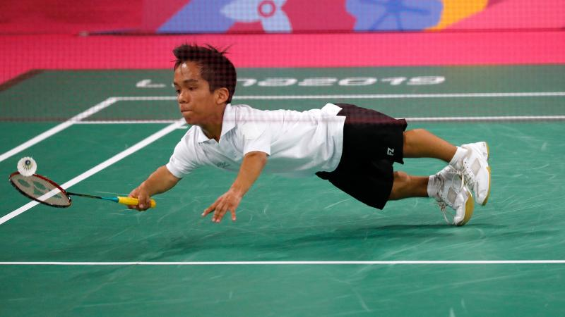 a male Para badminton player dives to hit a shot