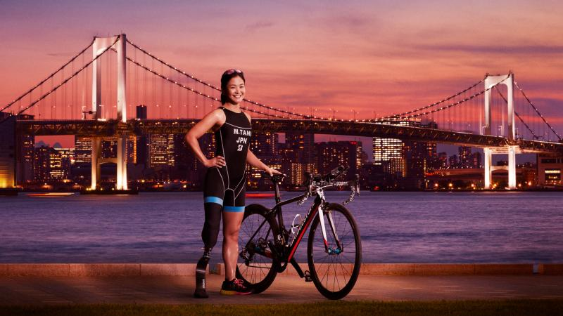 Japanese female triathlete poses with bridge in backdrop