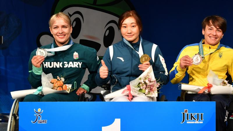 Four female wheelchair fencers holding up their medals