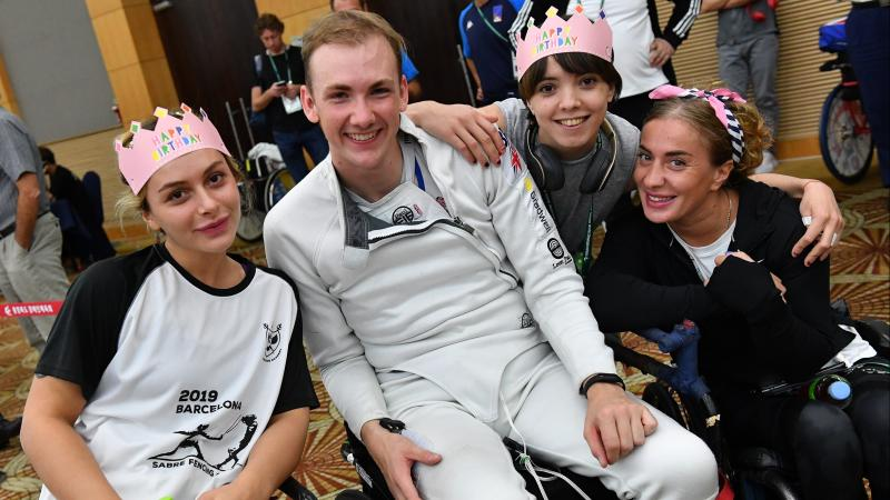 Male wheelchair fencer surrounded by friends for birthday