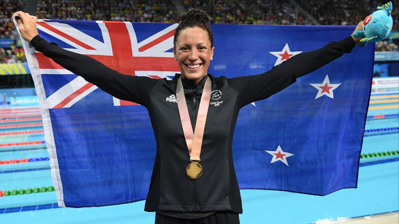 female Para swimmer holding up a New Zealand flag