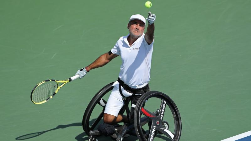 a male wheelchair tennis player throws the ball up to serve