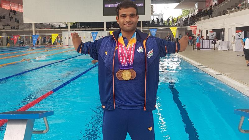 a male Para swimmer standing in front of a swimming pool with medals round his neck