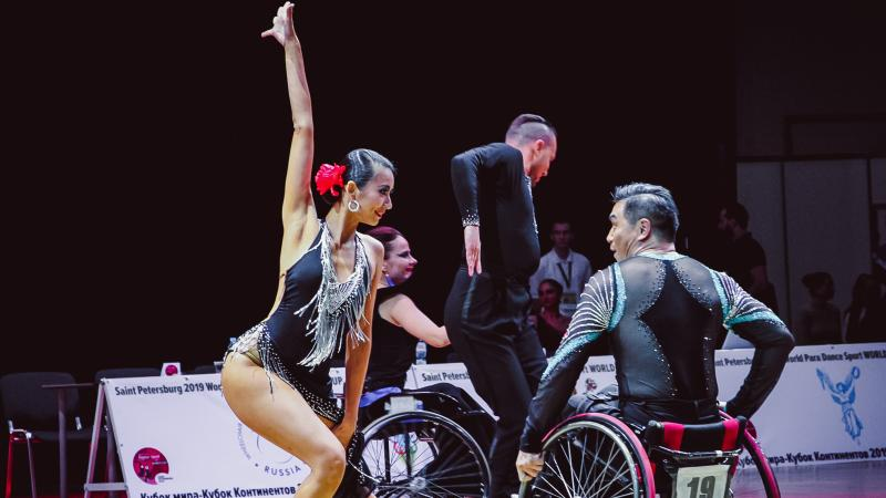 Female standing dancer dances with male wheelchair partner