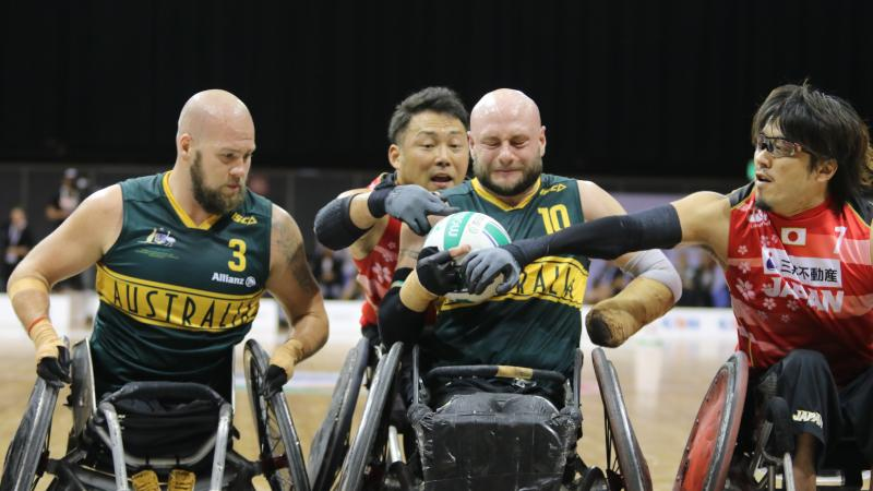Man tries to hold onto wheelchair rugby ball while defenders surround him